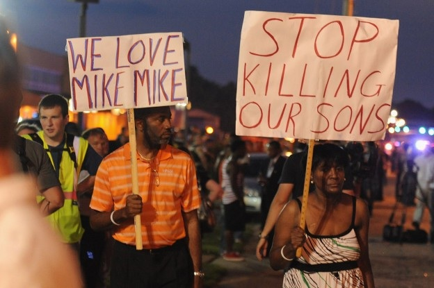 Demonstrators display signs during a protest on West Florissant Avenue in Ferguson, Missouri on August 18, 2014. Police fired tear gas in another night of unrest in a Missouri town where a white police officer shot and killed an unarmed black teenager, just hours after President Barack Obama called for calm. AFP PHOTO / Michael B. Thomas        (Photo credit should read Michael B. Thomas/AFP/Getty Images)