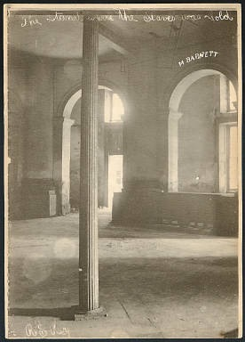 """The stand where the slaves was sold"" Location: 700 Canal Street, New Orleans, LA 70130, USA Date: 1900 / New Orleans was the largest slave market in the South. This photograph is of a room, possibly in the St. Charles Hotel, where slaves were sold up until the Civil War. (Source: New Orleans French Quarter Scenes, Mss. 2116) Created by LSU Libraries' Special Collections"